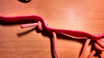 Tie a simple overhand knot once the cord is completely threaded